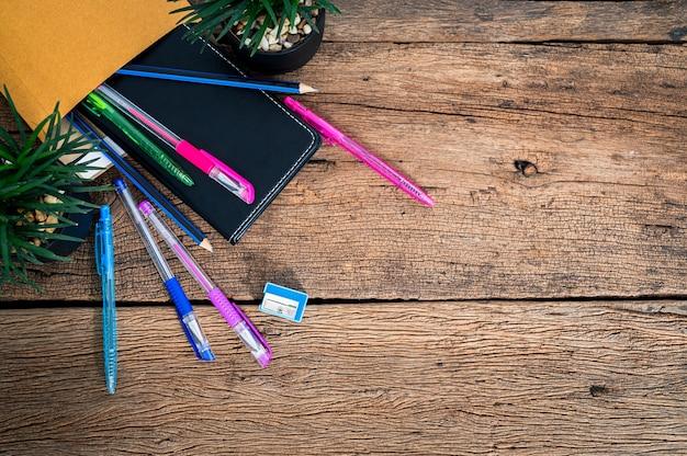 Suministros de papelería y libros de bolígrafos en el escritorio.