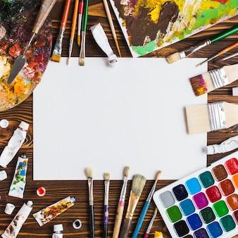 Suministros de pintura en la mesa alrededor de papel