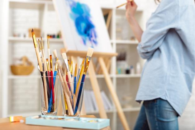 Suministros de pintura pinceles y caballete, lugar de trabajo del artista.