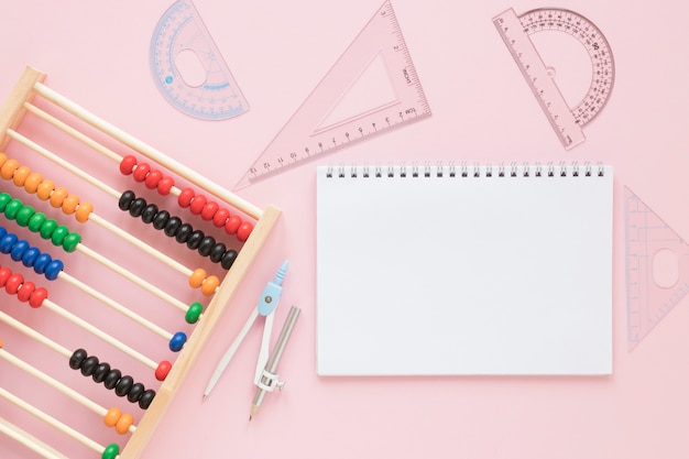 Suministros de reglas de matemáticas con ábaco y cuaderno vacío
