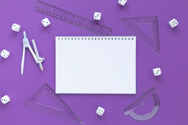 Suministros de reglas de matemáticas con dados y cuaderno vacío