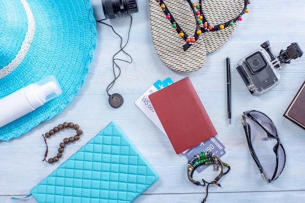 Suministros de viaje: sombrero, gafas de sol, chanclas, cámara, pasaporte sobre fondo azul