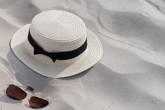 Sunglases, sombrero de paja de verano sobre fondo arenoso