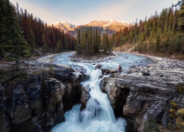 Sunwapta falls es un par del río sunwapta con un viajero de pie en el bosque de otoño al atardecer