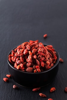 Súper cerebro alimento seco goji berry en taza de cerámica negra en pizarra pizarra