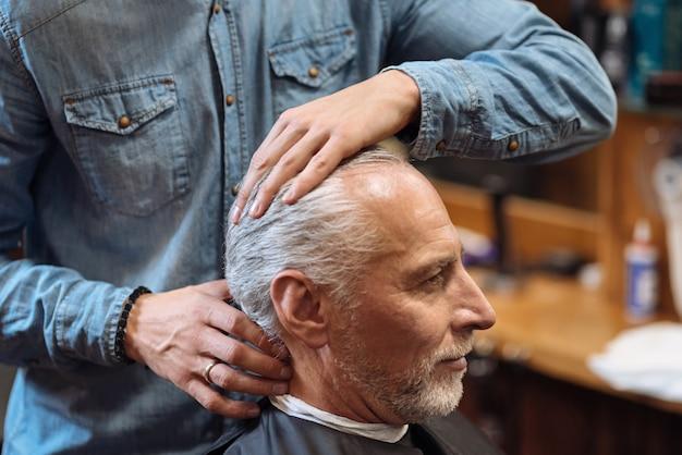 Super fijación. cerca de joven barbero vistiendo denim peinado cabello de cliente senior en barbería