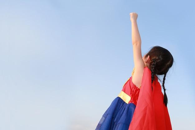 Super héroe de la muchacha del pequeño niño en un gesto para volar en fondo claro de cielo azul. concepto de superhéroe infantil.
