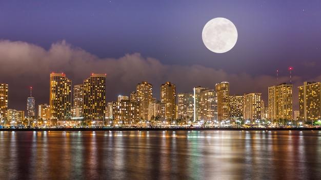 Super luna llena sobre el centro de honolulu en la noche