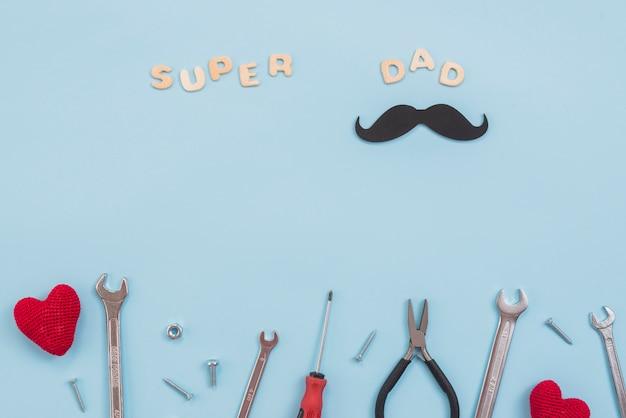 Súper papá inscripción con herramientas y bigote de papel.