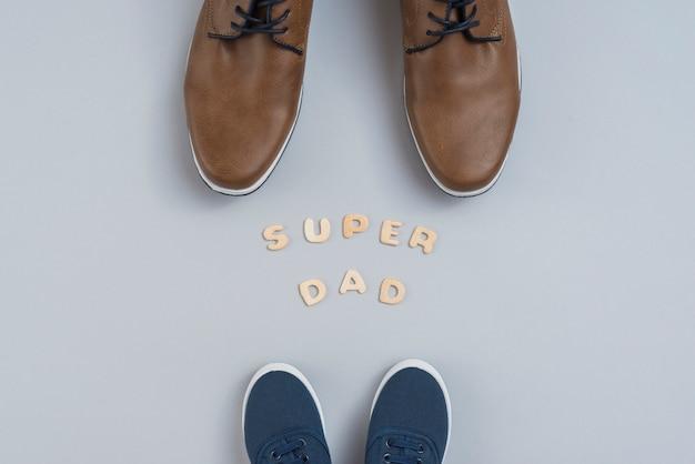 Súper papá inscripción con zapatos de hombre y niños.