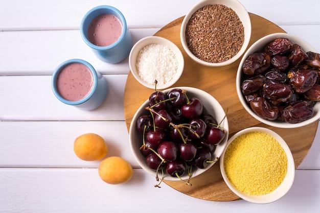 Superalimentos en tazones, frutas frescas y batido de bayas sobre fondo blanco de madera.
