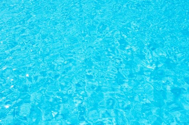 Superficie del agua azul de la piscina con el reflejo de luz del sol brillante.