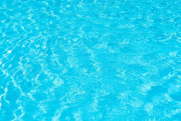 Superficie de agua de la piscina con reflejos de luz brillante