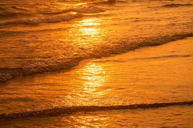 Superficie del agua en la playa en la hora del atardecer.