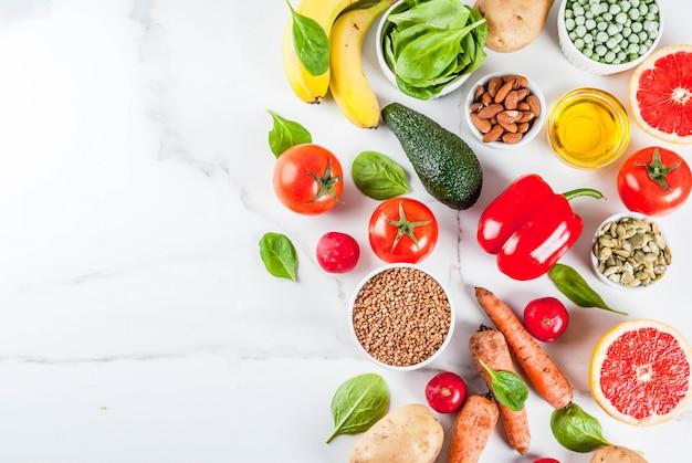 Superficie de alimentos saludables, productos de dieta alcalina de moda: frutas, verduras, cereales, nueces. aceites, superficie de mármol blanco arriba