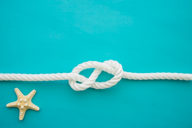 Superficie azul con estrella de mar y cuerda blanca