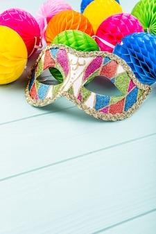 Superficie azul festiva con máscara de carnaval colorida y bolas de pimienta. concepto de tarjeta de felicitación para cumpleaños, carnaval, fiesta, invitación