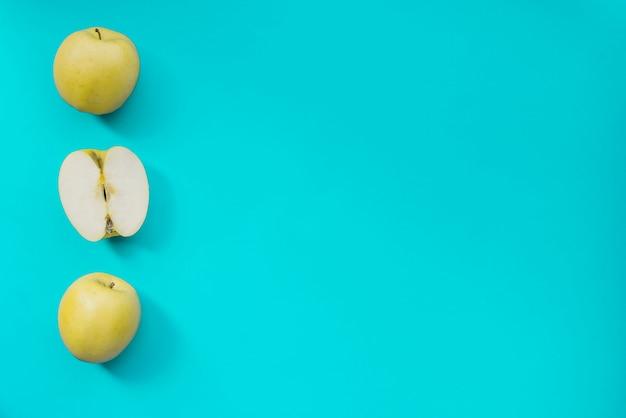 Superficie azul con manzanas verdes