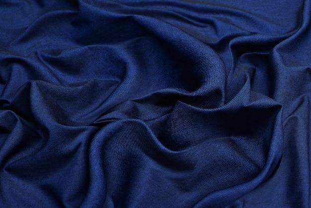 Superficie azul de la tela. fondo de textura de fondo ondulado de ropa