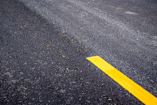 Superficie de la carretera de asfalto con línea amarilla