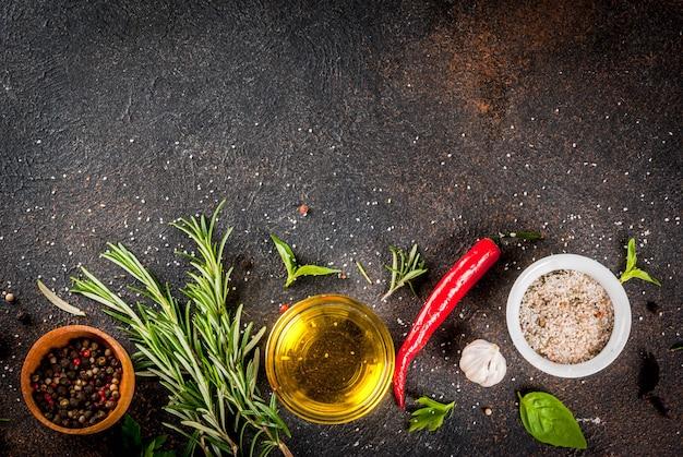 Superficie de cocción, hierbas, sal, especias, aceite de oliva, superficie oxidada oscura