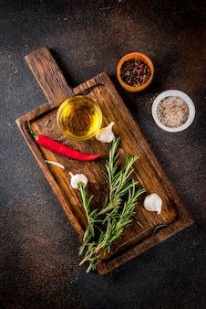 Superficie de cocción, hierbas, sal, especias, aceite de oliva en tabla de cortar