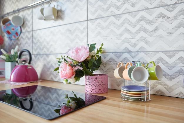 La superficie de la cocina con una encimera negra. flores y tazas en la mesa de la cocina.