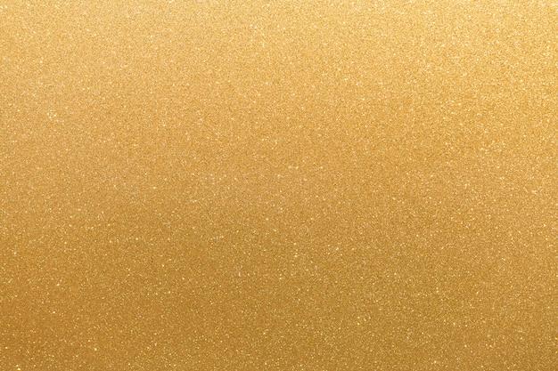 Superficie de color amarillo anaranjado con brillo dorado con manchas irregulares blancas parpadeantes