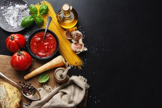 Superficie de comida italiana con espaguetis y salsa de tomate sobre fondo oscuro