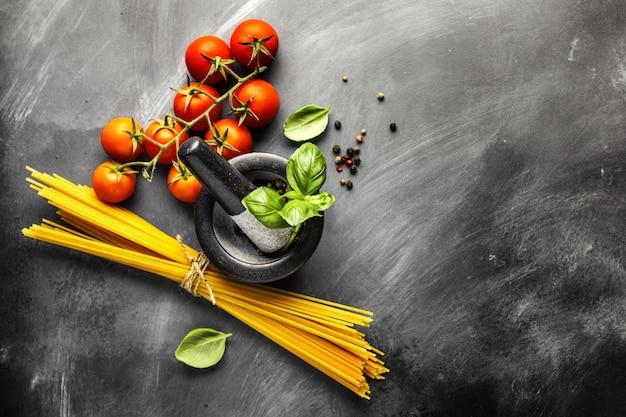 Superficie de comida italiana con ingredientes para cocinar en la superficie oscura. vista desde arriba. concepto de cocina