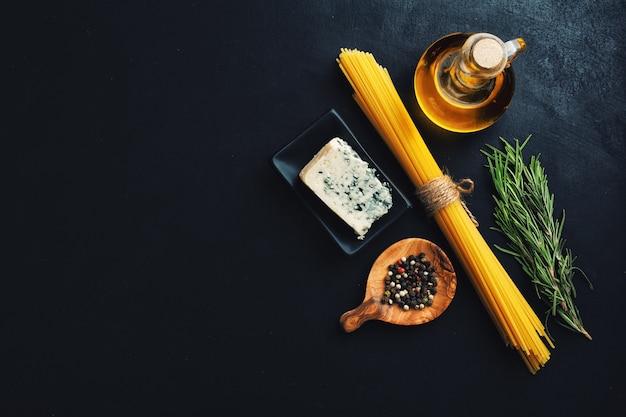 Superficie de comida italiana con verduras, queso y pasta en superficie oscura