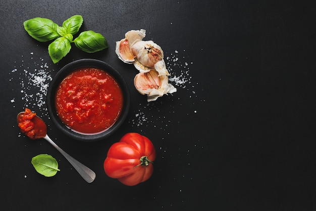 Superficie de comida italiana con verduras y salsa de tomate sobre superficie oscura
