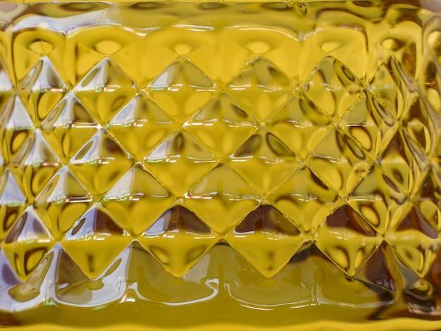 Superficie de forma de patrón ceñido de fondo de botella de aceite dorado