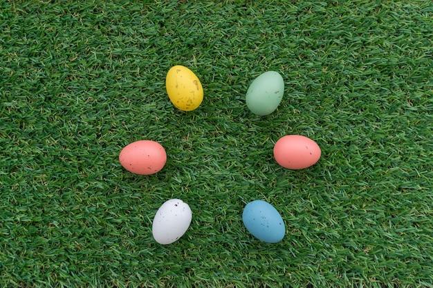Superficie de hierba con seis huevos de colores para el día de pascua