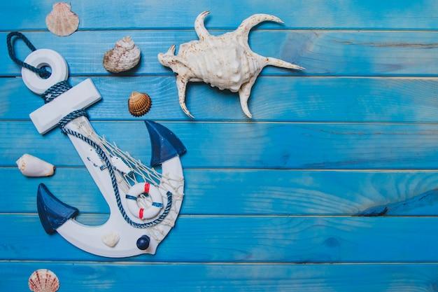 Superficie de madera azul con conchas marinas y ancla