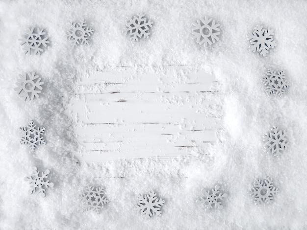 Superficie de madera blanca de navidad con nieve y copos de nieve. vista superior, espacio de copia, espacio de texto vacío.