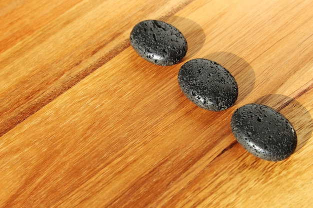 Superficie de madera con cuentas de lava negras en un salón de spa, ideal para fondo o papel tapiz