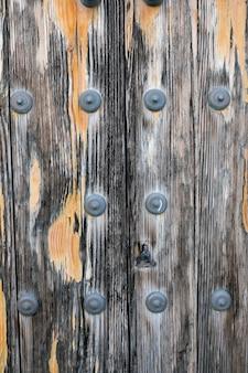 Superficie de madera envejecida con remaches metálicos.