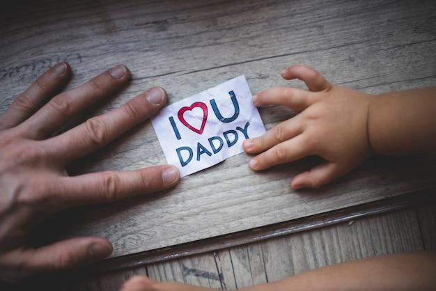 Superficie de madera con manos y nota bonita para el día del padre