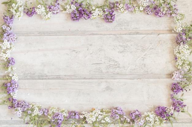 Superficie de madera con marco hecho de flores blancas y moradas