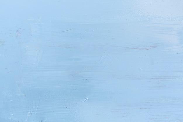Superficie de madera pintada con trazos de pintura.