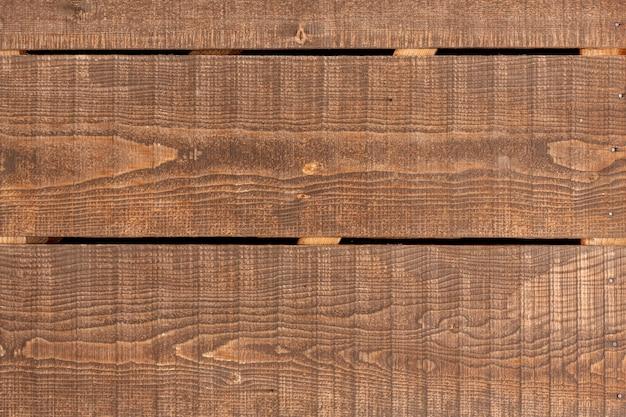 Superficie de madera con vetas y clavos.