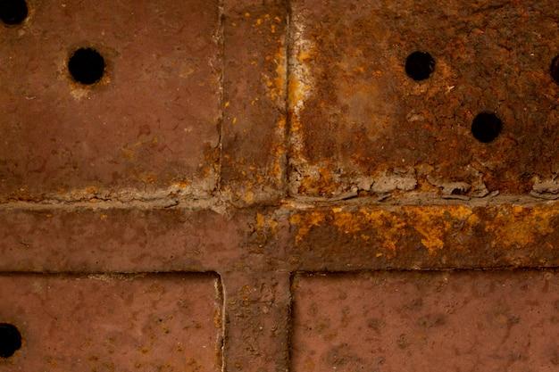 Superficie de metal oxidado con soldadura y agujeros