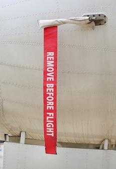 Superficie metálica de un avión militar con cinta roja advertencia de precaución
