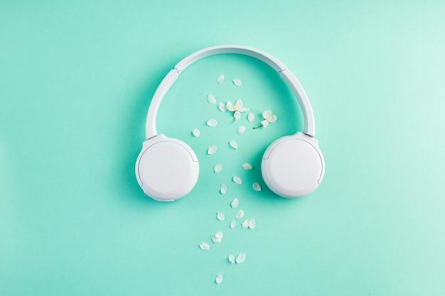 Superficie de música o podcast con auriculares con flor de cerezo en superficie turquesa