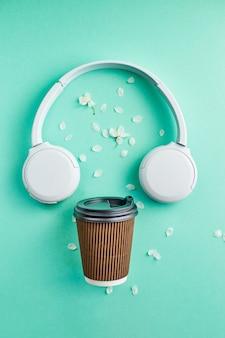 Superficie de música o podcast con auriculares y taza de café de papel con flor de cerezo en superficie turquesa vista superior plana