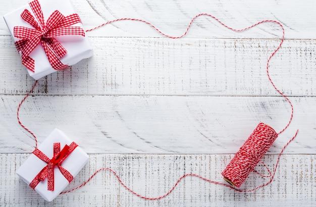 Superficie de navidad con cinta roja, juguetes, cajas de regalo y piñas en la mesa de superficie vieja de madera blanca. enfoque selectivo.