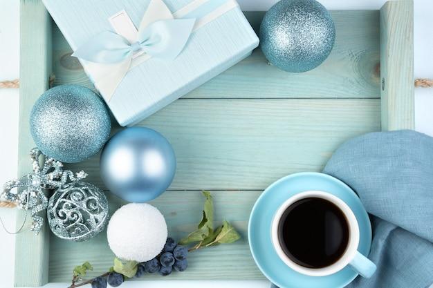 Superficie navideña con una caja de regalo, una taza de bolas de café y una rama con bayas en una bandeja azul suave