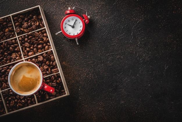 Superficie oscura con granos de café, un reloj despertador y una taza de café.