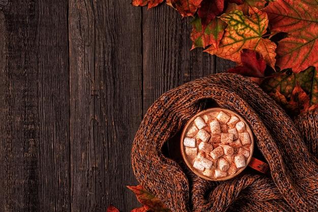 Superficie de otoño con chocolate caliente, bufanda de punto, hojas multicolores